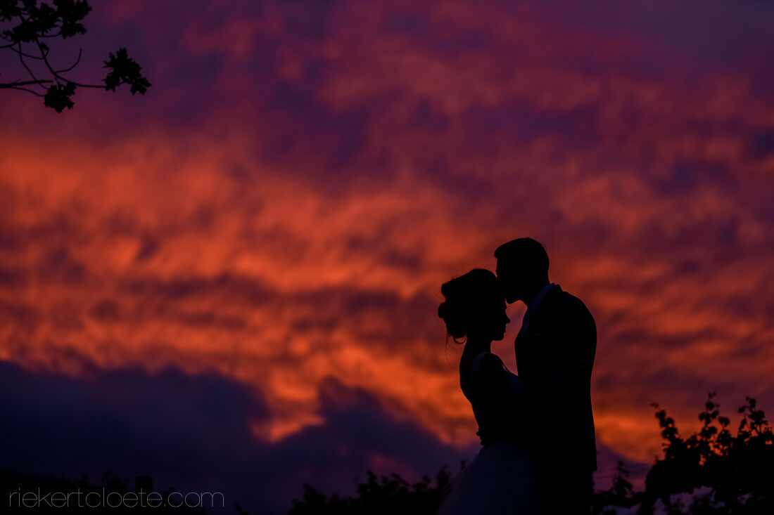 Groom kissing Bride at night with amazing sunset