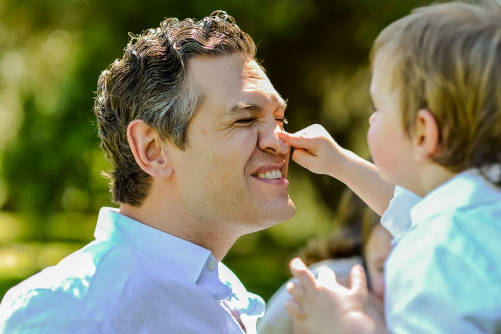 Boy poking father's nose