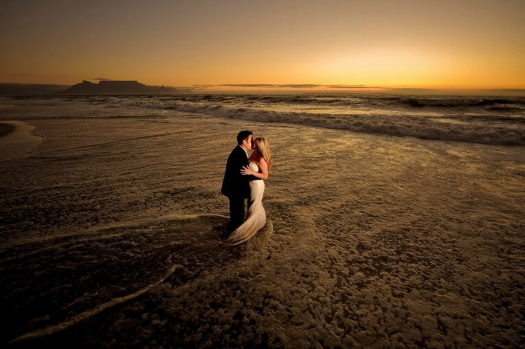 Bride and groom in small wave at beach during sunset