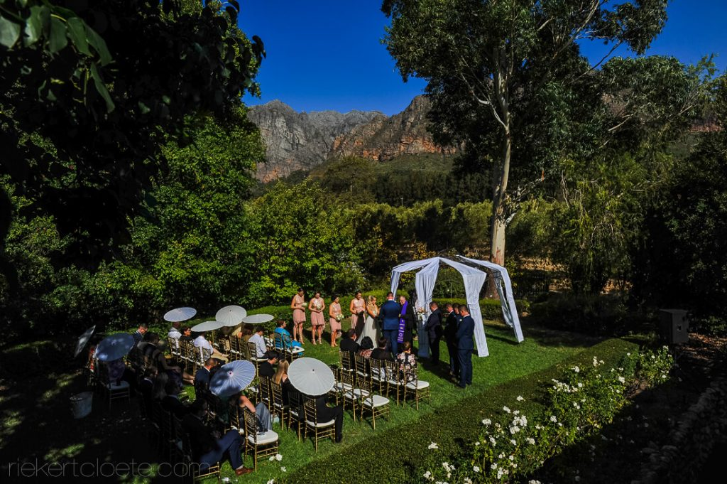 Ceremony between trees with mountains in the background