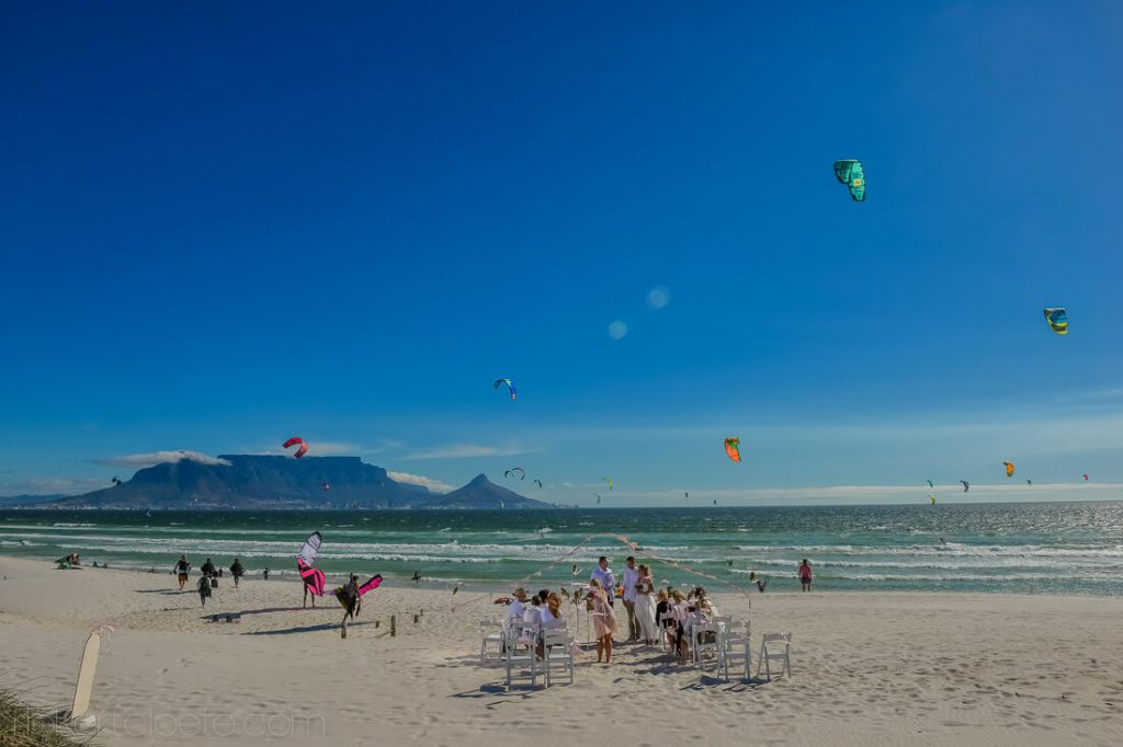 flying kites at a beach wedding, mountain in the background