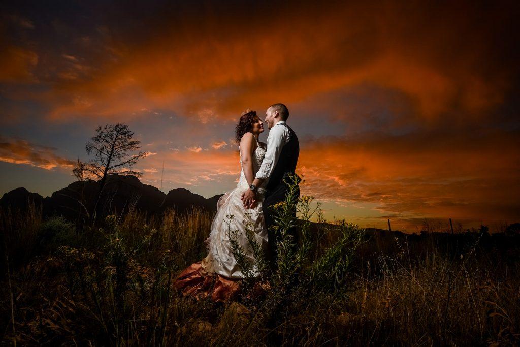 Wedding couple kissing, sunset background