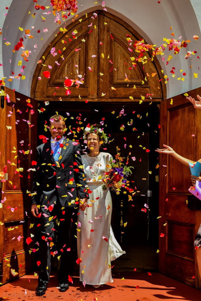 Bride and groom leaving church thrown with flower petals